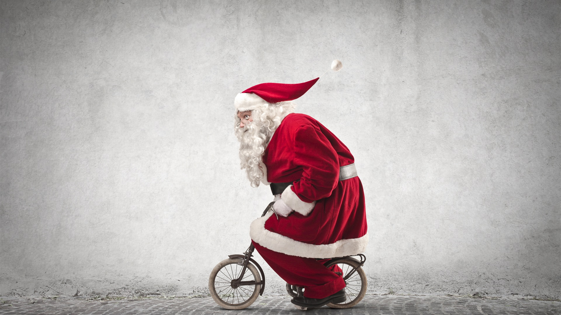 Santa-Claus-riding-a-small-bike-humor-red-coat-glasses-Christmas-theme_1920x1080.jpg